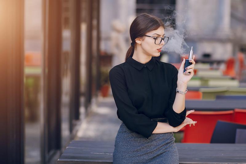 街角で電子タバコを吸う女性
